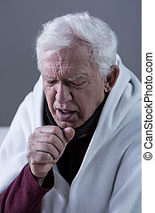 Coughing man covered with blanket - Ill coughing senior man...