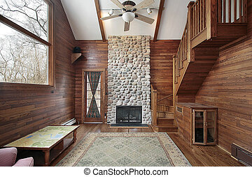 Wood paneled family room with stone fireplace