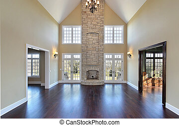Family room in new construction home with two story stone...