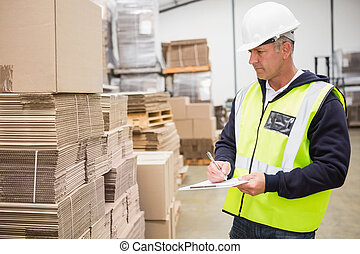 Warehouse worker checking his list on clipboard in a large...