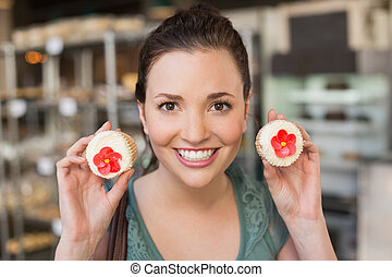 Pretty brunette showing cupcakes at the bakery