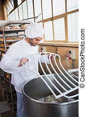 Baker preparing dough in industrial mixer