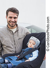 Father carrying baby in his car seat smiling at camera