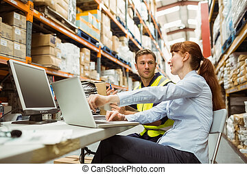 Warehouse worker and manager looking at laptop in a large...