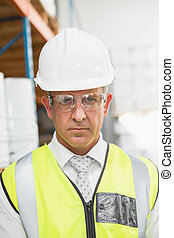 Manager wearing hard hat in warehouse - Close up portrait of...