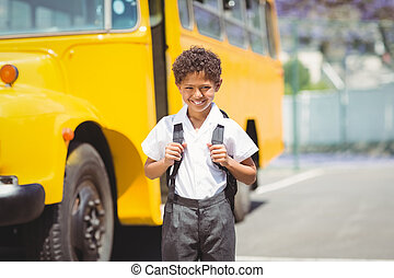 Cute pupil smiling at camera by the school bus outside the...