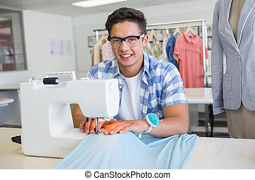 Fashion student using sewing machine at the college