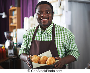 Selling pastry - Happy African-american guy with croissants