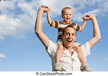 Father son piggy back - Father carrying his son on piggy...