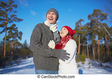 Couple in winterwear - Ecstatic man and woman in knitted...