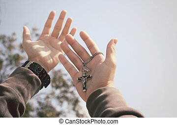 Hands reaching with cross