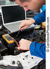 Mechanic using diagnostic tool on engine at the repair...