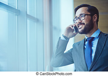 Communication - Smiling businessman in eyeglasses talking on...