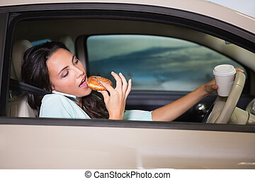 Woman drinking coffee and eating donnut on phone in her car