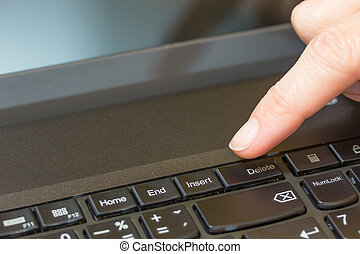 Pressing the Delete key on the keyboard of a laptop - Women...