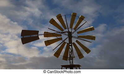 Old ranch windmill on a sky background   (time lapse)
