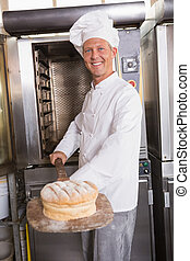 Happy baker taking out fresh loaf in the kitchen of the...