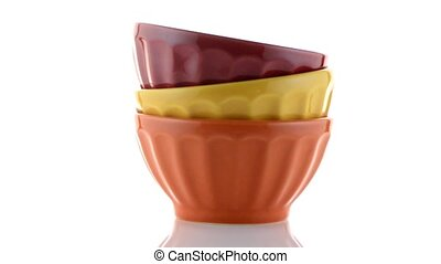 Three colored bowls on white reflective background