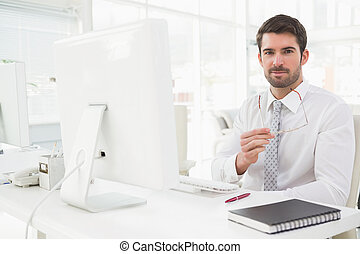 Smiling businessman well dressed sitting in his office