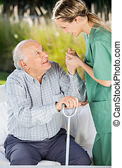 Female Caretaker Helping Senior Man To Get Up From Couch -...