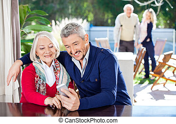 Smiling Grandson And Grandmother Using Smartphone - Smiling...