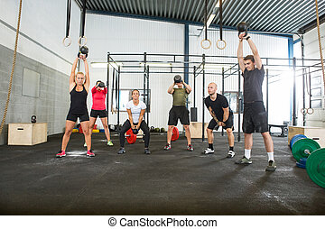 Athletes Lifting Kettlebells in Cross Fitness Box - Group of...