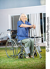 Senior Woman Sitting On Wheelchair At Nursing Home Lawn -...