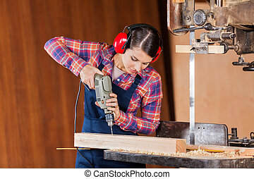 Carpenter Drilling Wood At Bandsaw - Young female carpenter...