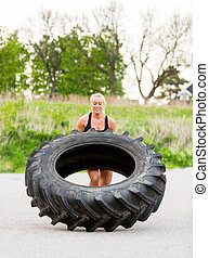 Athlete Doing Tire-Flip Exercise On Street - Young female...