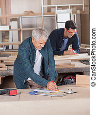 Male Carpenter Working On Blueprint At Workshop - Senior...