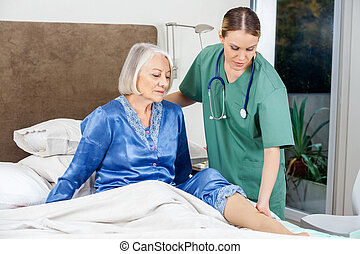 Caretaker Examining Senior Woman's Leg