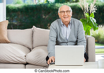 Smiling Senior Man With Laptop At Nursing Home Porch -...