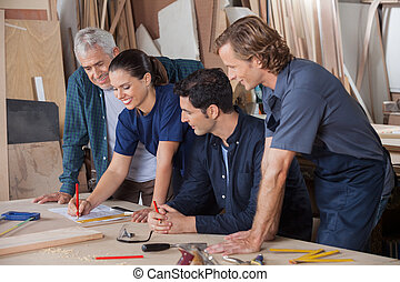 Carpenters Working On Blueprint - Team of carpenters working...