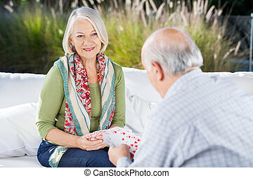 Happy Senior Woman Playing Cards With Man - Happy senior...