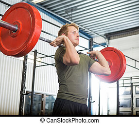 Man Lifting Barbell At Gym - Fit young man lifting barbell...