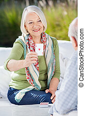 Smiling Senior Woman Playing Cards With Man