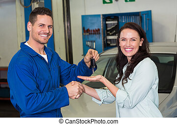 Mechanic and customer smiling at camera at the repair garage