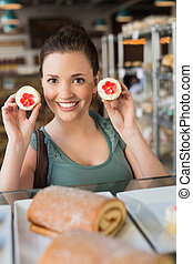 Pretty brunette showing a cupcake at the bakery