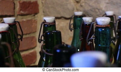 Green bottles with a vintage cap. Brick background.