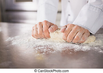 Close up of baker preparing dough in the kitchen of the...
