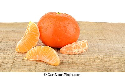 Mandarine with pieces isolated on wooden table - Studio shot...