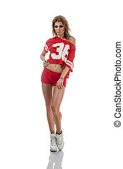 Beautiful young cheerleader in a red uniform with long hair....