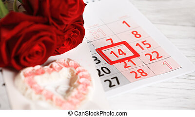 red roses lay on the calendar with the date of February 14...