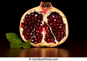 Half-cutted pomegranate with green leaf over dark background