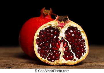 Grenadines - Whole and half-cutted pomegranate on rustic...