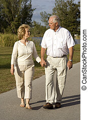 Retirement - Happy senior couple walking in a park