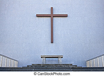 Cross on exterior wall of Cathedral - Cross with bench on...