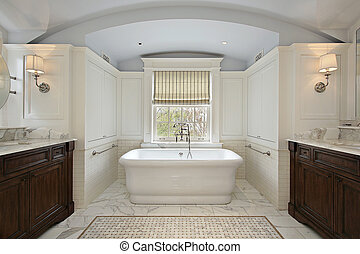 Master bath in luxury home with white tub