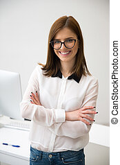Attractive happy businesswoman standing with arms folded in office