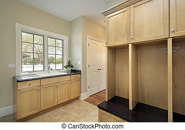 Mud room in new construction home with oak cabinetry